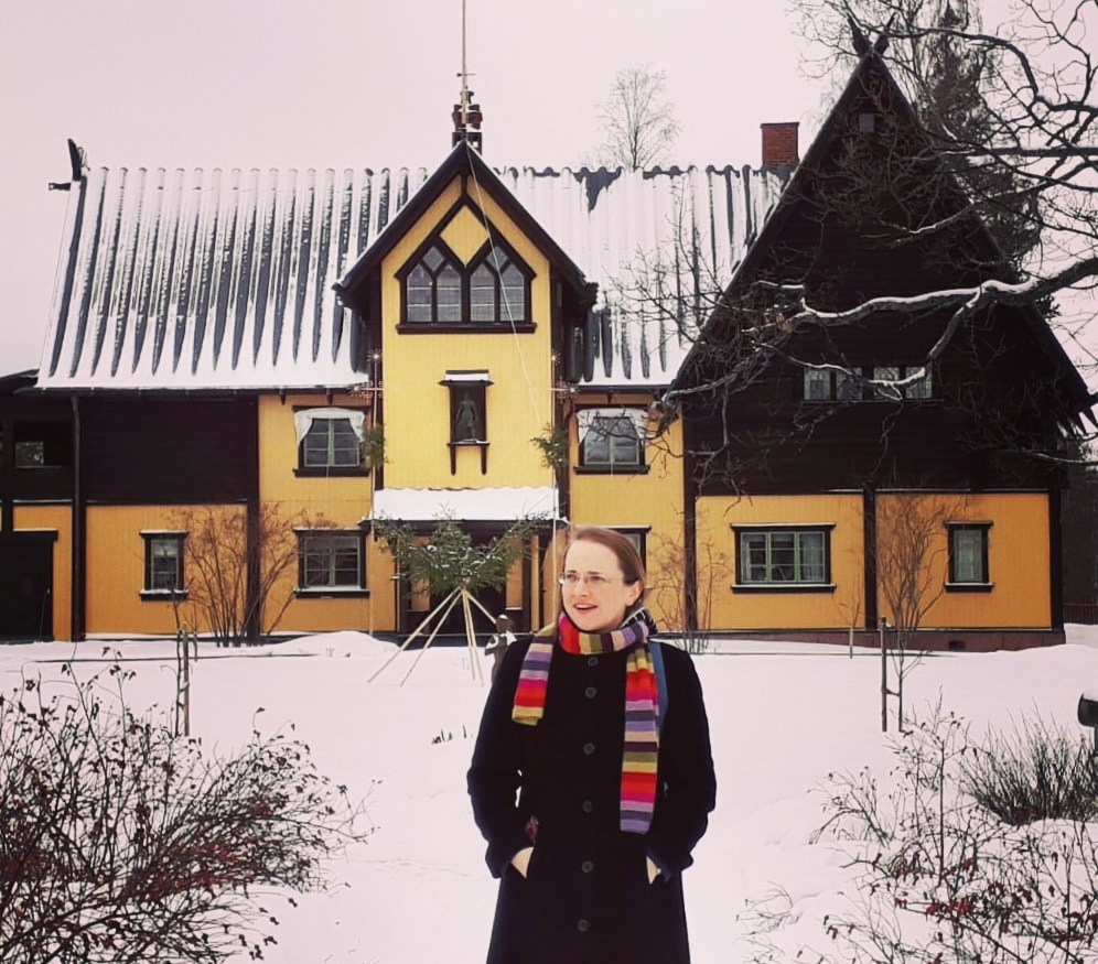 The author Anca Rusu outside a yellow house with snow in Mora