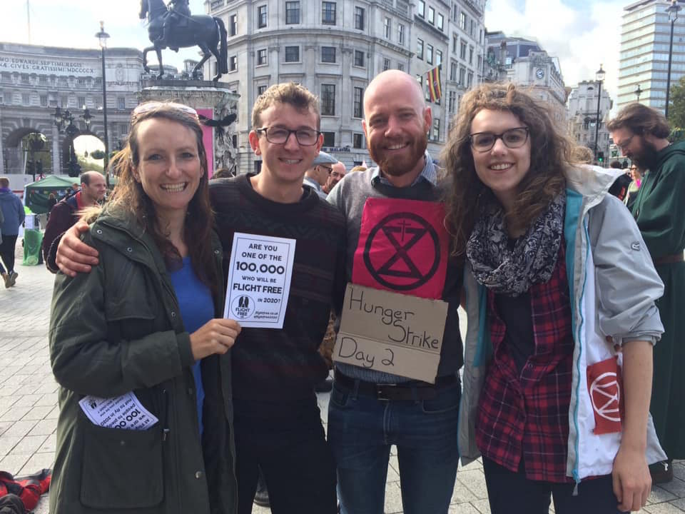 Picture shows Anna Hughes, Neil, Eddie and Helen at a Christian Climate Action event. They are smiling with their arms around each other and Anna is holding a Flight Free Pledge page in her hand. Eddie has a sign round his neck which reads 'hunger strike day 2'. There are people chatting behind them and they are outside.