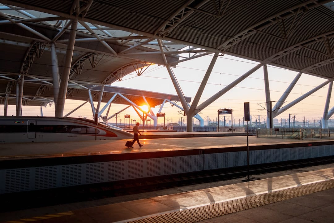 A passenger is walking across a rail platform in a Chinese train station. It is dusk and the sun is shining through the structure of the platform roof.