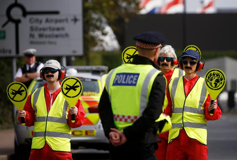 Protestors block the streets wearing hi vis jackets, head phones and pretending to be flight conductors. The police look on.