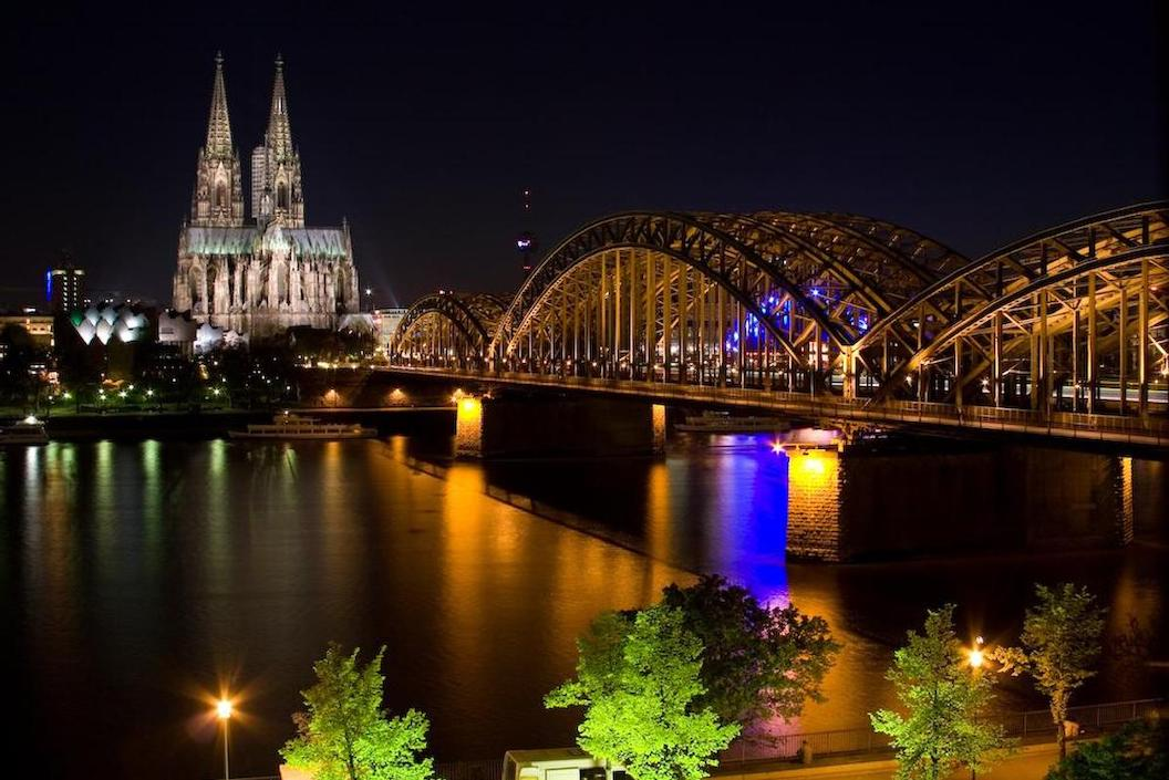 Picture shows a river, a bridge and a lit up cathedral in the city of Cologne. It is night time and the city is lit up with blue and yellow lights. There are illuminated trees in the foreground.