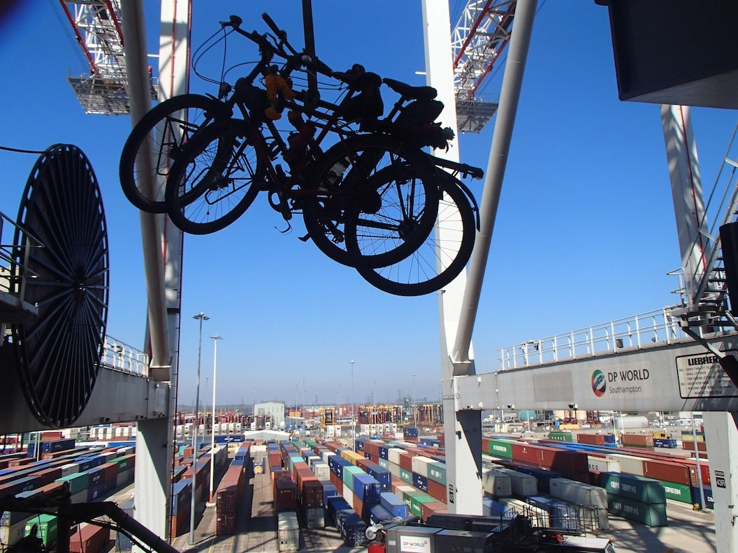 Picture shows two bikes being lifted over a large container ship. The sky is blue and the ship appears to large that you cant see where it ends.