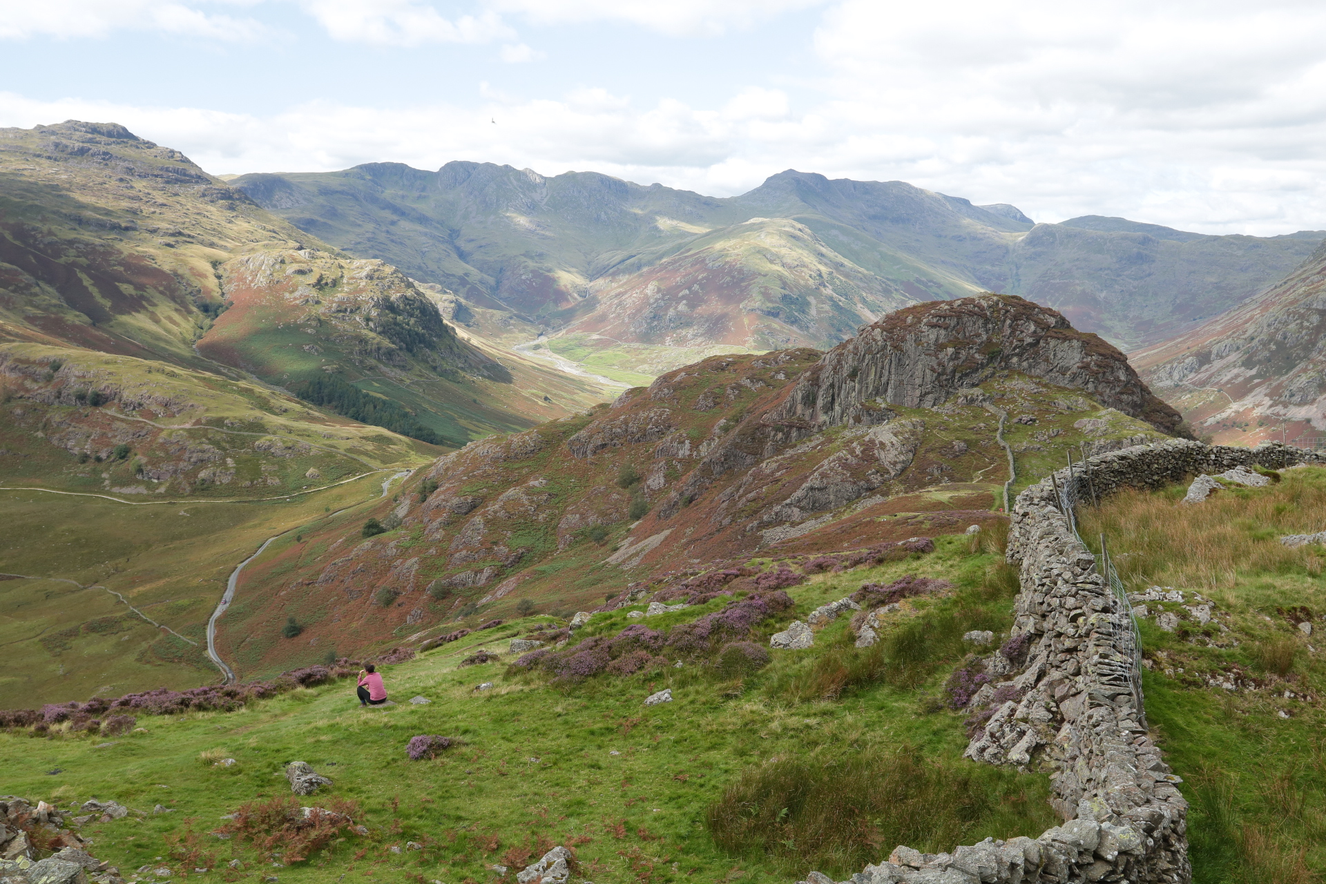Image shows a wide view of the Lake District mountains. The grass is green with purple and red shrubs. Deep valleys are visible and the sun is shining in spots around the hills. You can see Sophia sitting on a rock.