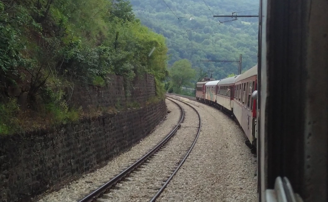 Picture shows a view of train tracks cutting through tree covered hills.