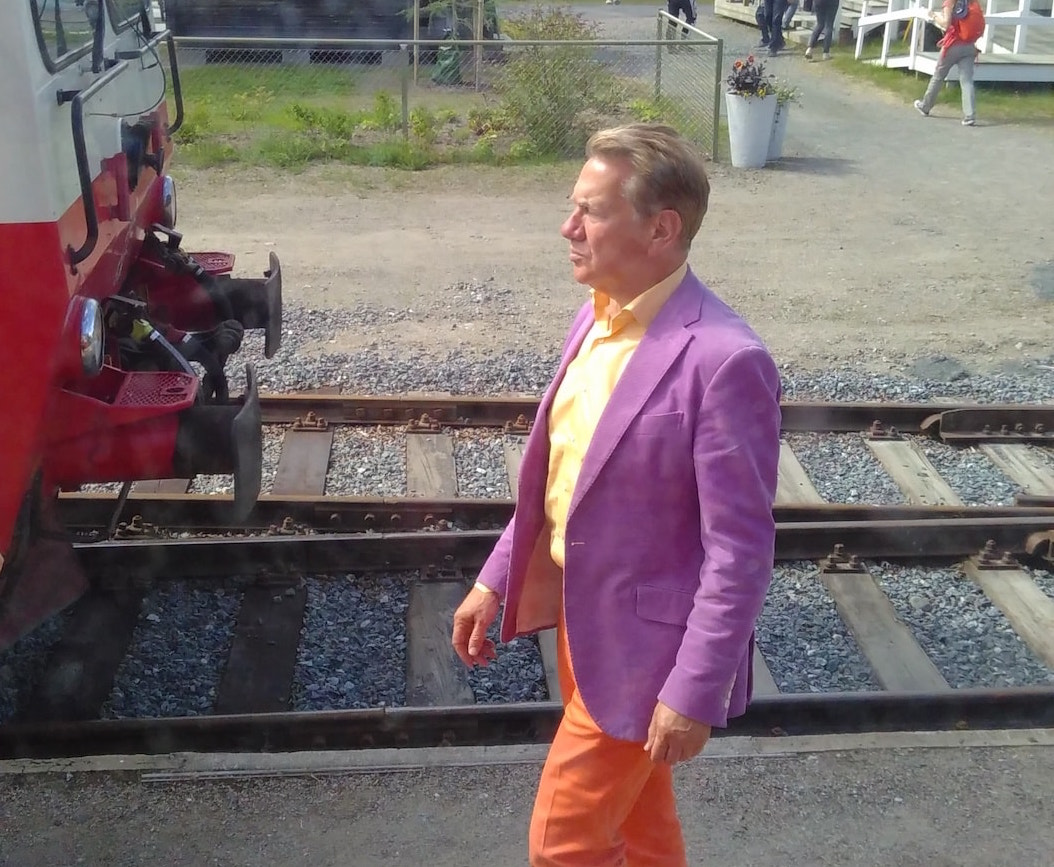 Picture shows Michael Portillo walking along next to train tracks. In the background are people walking in and out of a cafe.