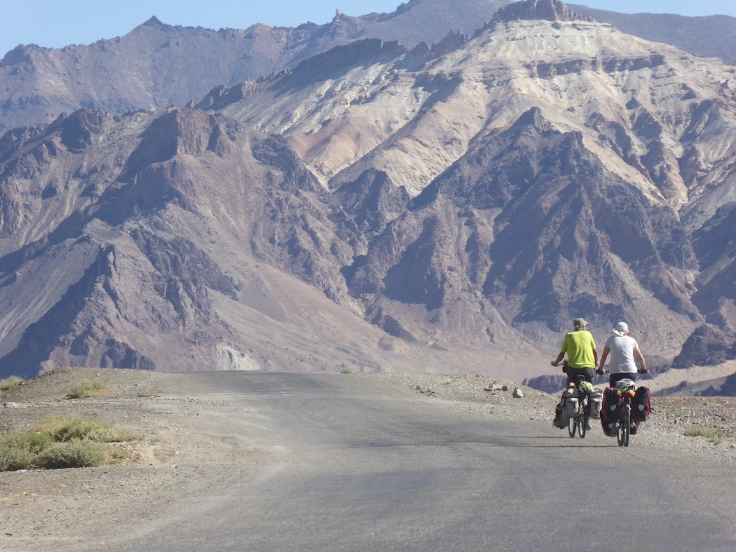 Picture shows Christine and Peter cycling along a dusty road in Tajikistan. They have their backs to the camera and in front of them is a vast mountainous landscape.
