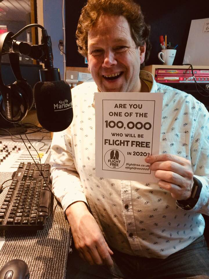 Picture shows Dave holding a piece of paper with the Flight Free 2020 pledge on it. He is sitting in a recording booth for his radio show and smiling.