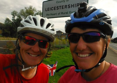 Debs and Jo on their bikes in front of the Leicestershire county sign