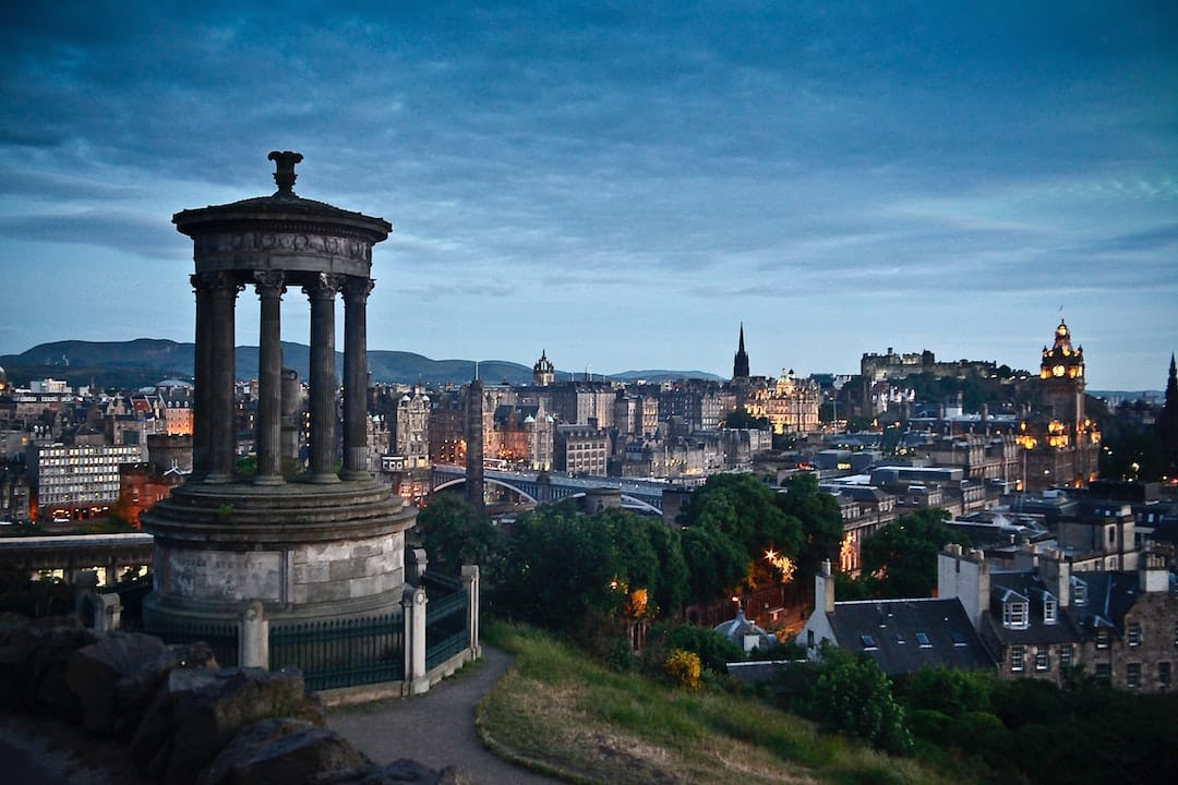 Picture shows a cityscape of Edinburgh. Its dusk and the sky is gloomy.