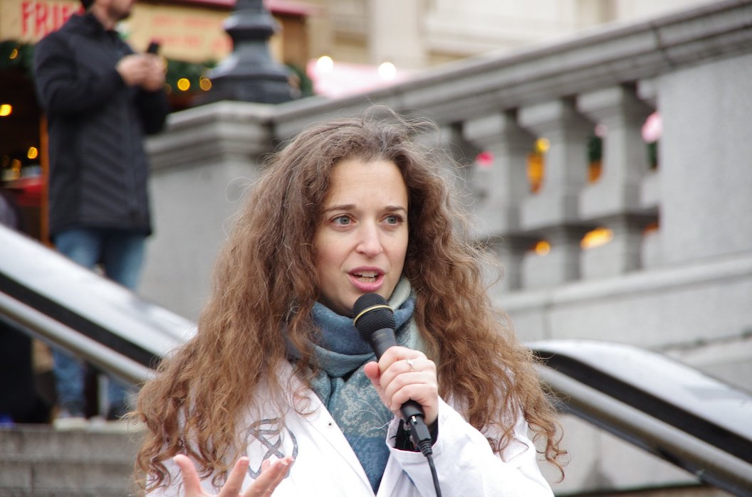 Dr Emily Grossman is speaking at an Extinction Rebellion protest, she is wearing a lab coat with the XR logo on it, and holding a microphone.