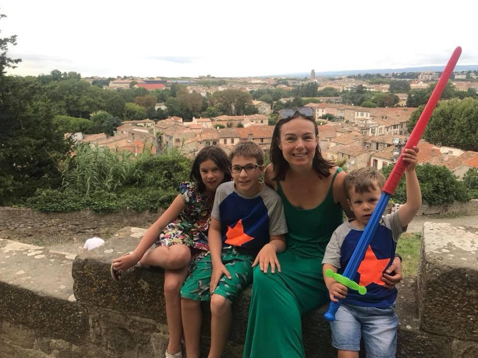 Eve and her three children are smiling and sitting on a wall overlooking Avignon.