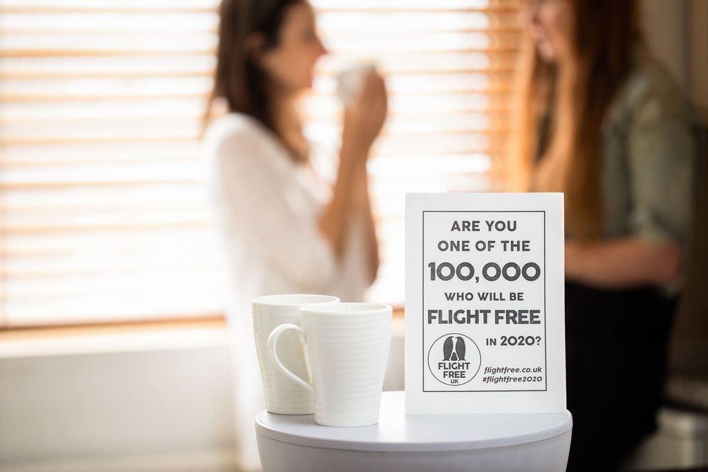 A piece of paper with the Flight Free 2020 pledge on it is resting on a copy table next to a mug. In the blurred background stand two women drinking coffee and chatting.