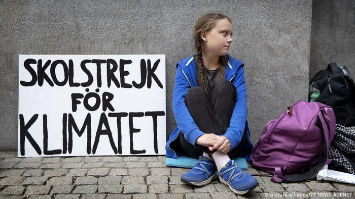 Picture shows Greta Thunberg outside the Swedish parliament. She is sitting crossed-legged on the street with her 'school strike for climate' sign. Next to her is a purple rucksack.
