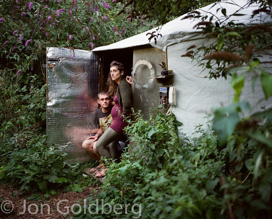 Picture shows a couple standing in the doorway to their cabin. The cabin is made of wood and is lined with silver insulation and is surrounded by budlia and other plants
