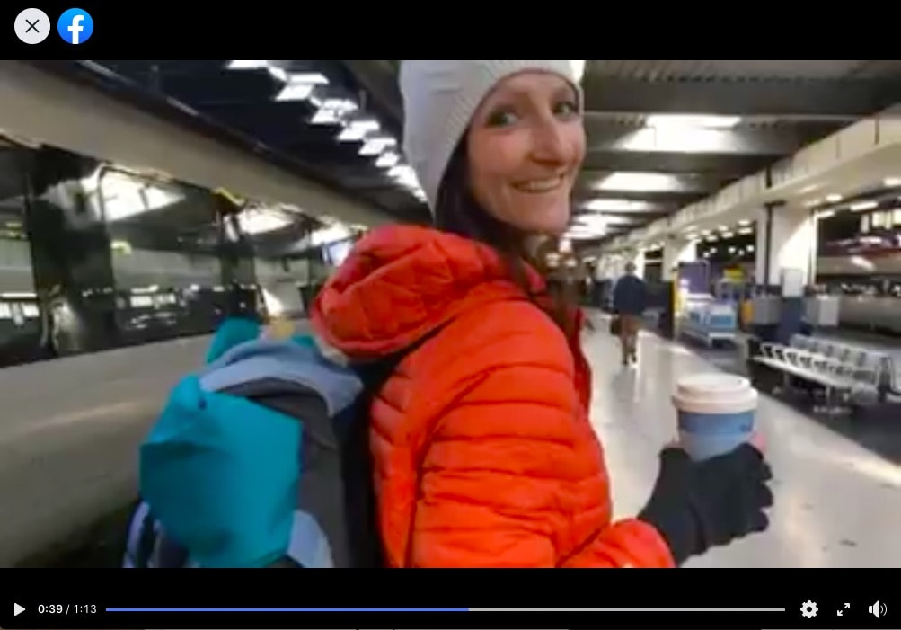 The image is a screenshot from the video on facebook mentioned below. Anna Hughes is turning around to the camera and smiling, wearing an orange puffer coat and carrying a cup of coffee. She is in a station.