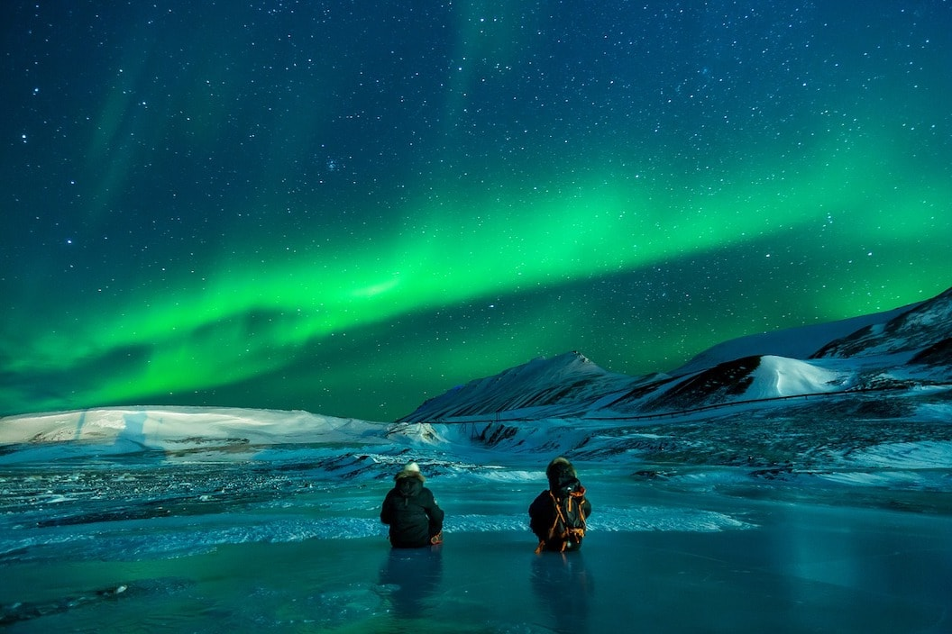 The picture shows the Northern Lights. To figures crouch near  shallow pool wearing many layers. It is night and there are great waves of green light in the sky.