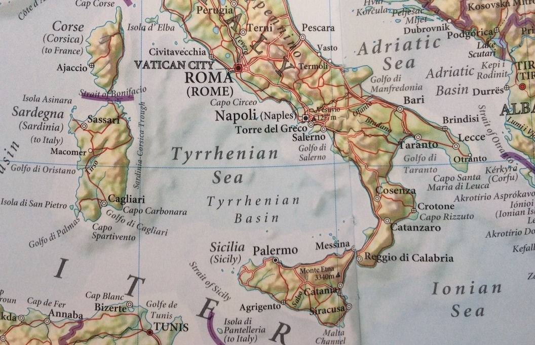 The picture shows a closeup shot of a map of Italy, with Sicily at the bottom.