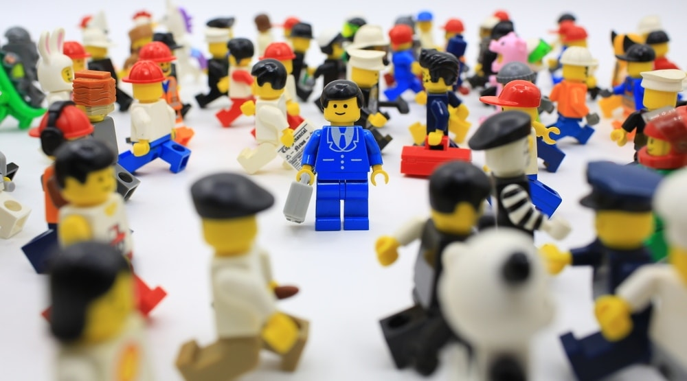 Picture shows a crowd of lego figures. Standing in the middle of the crowd with the camera focused upon it, is a lego figure of a man wearing a blue suit and carrying a briefcase.