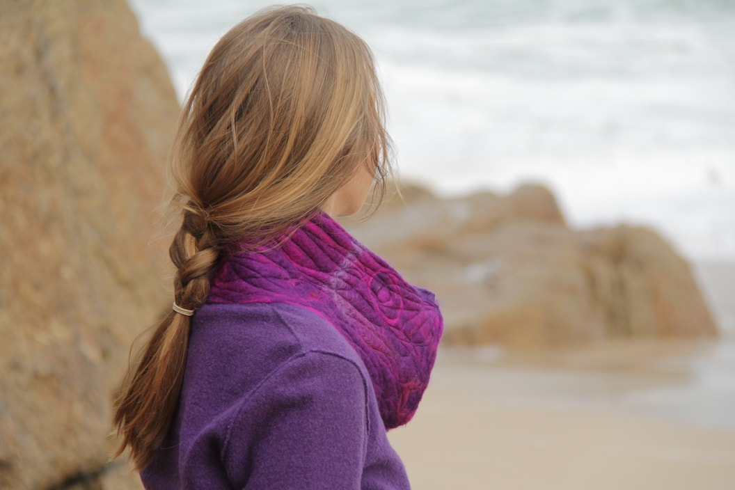 Picture shows a women wearing a purple jumper and a purple scarf. She is on the beach looking out to the sea and she has her back to the camera.