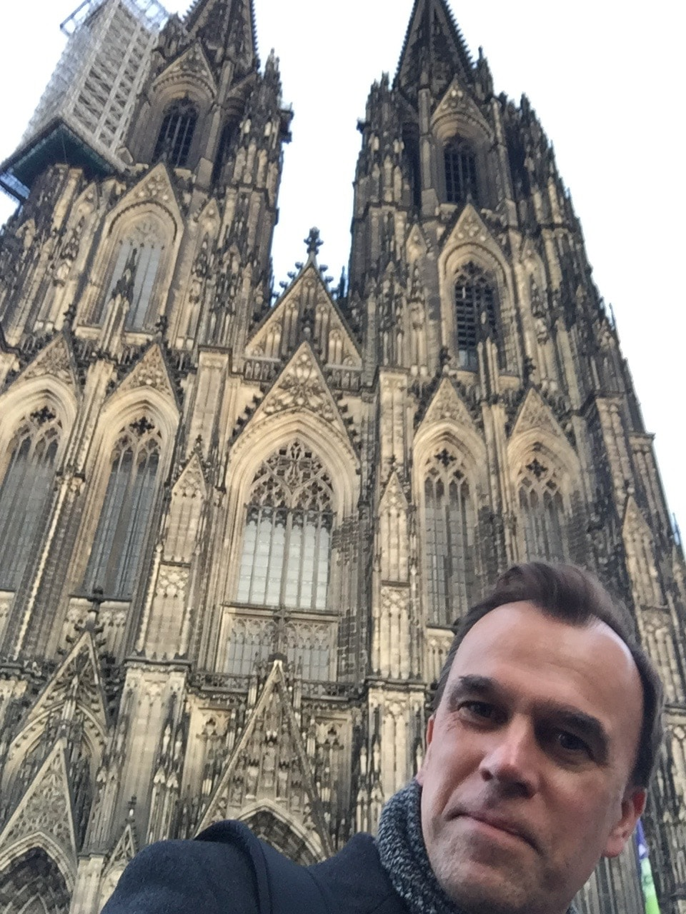 Picture shows a selfie taken by Martin, in the background is a large cathedral in Cologne. Martin is in the foreground smiling, wearing a coat and scarf.