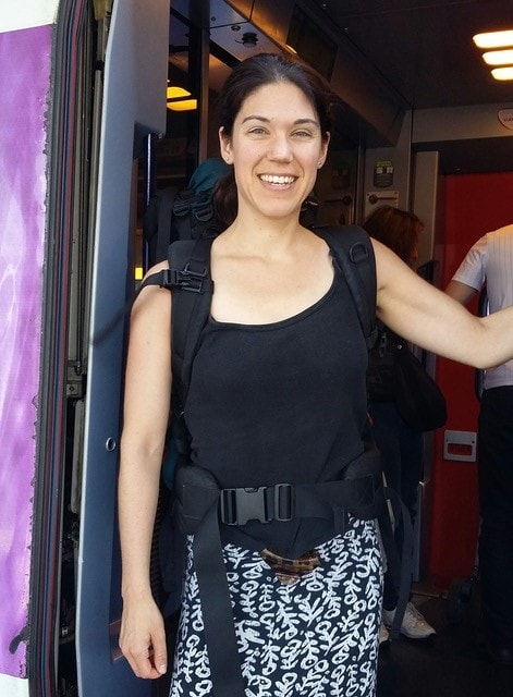 Milena is standing in the doorway of a train smiling and wearing a large rucksack.