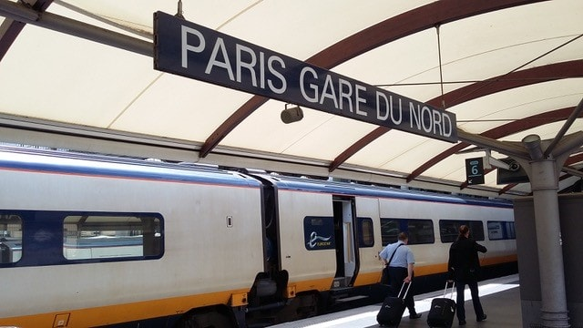 "Picture shows a parked train on a platform with the sign saying ""Paris Gare Du Nord""."