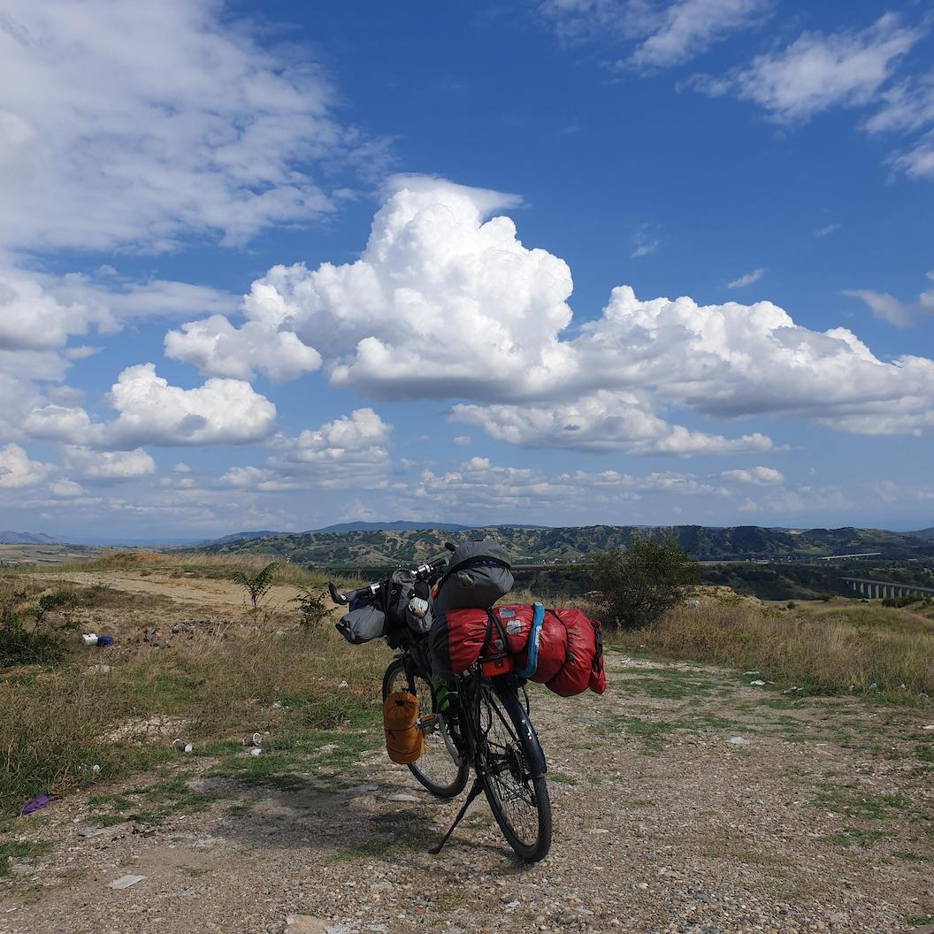 Picture shows a bicycle leaning on its stand packed with camping equipment. Behind it is a grassy and gravelly landscape with rolling hills in the background.