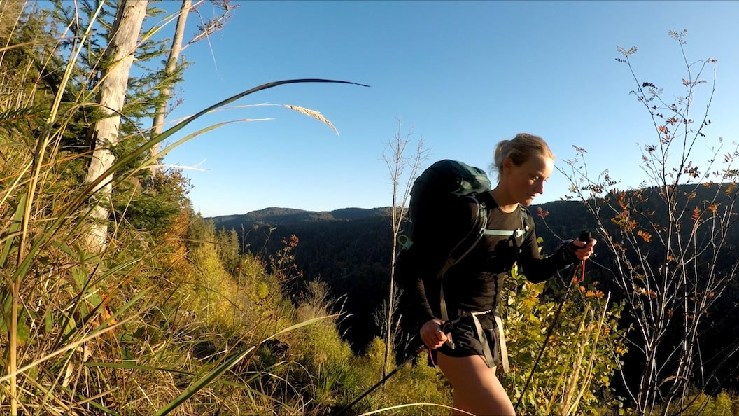 Picture shows Rosie hiking through tall grass on a sunny hillside. She is wearing activewear and carrying a large rucksack. There are tall hills in the background and the sky is bright blue.