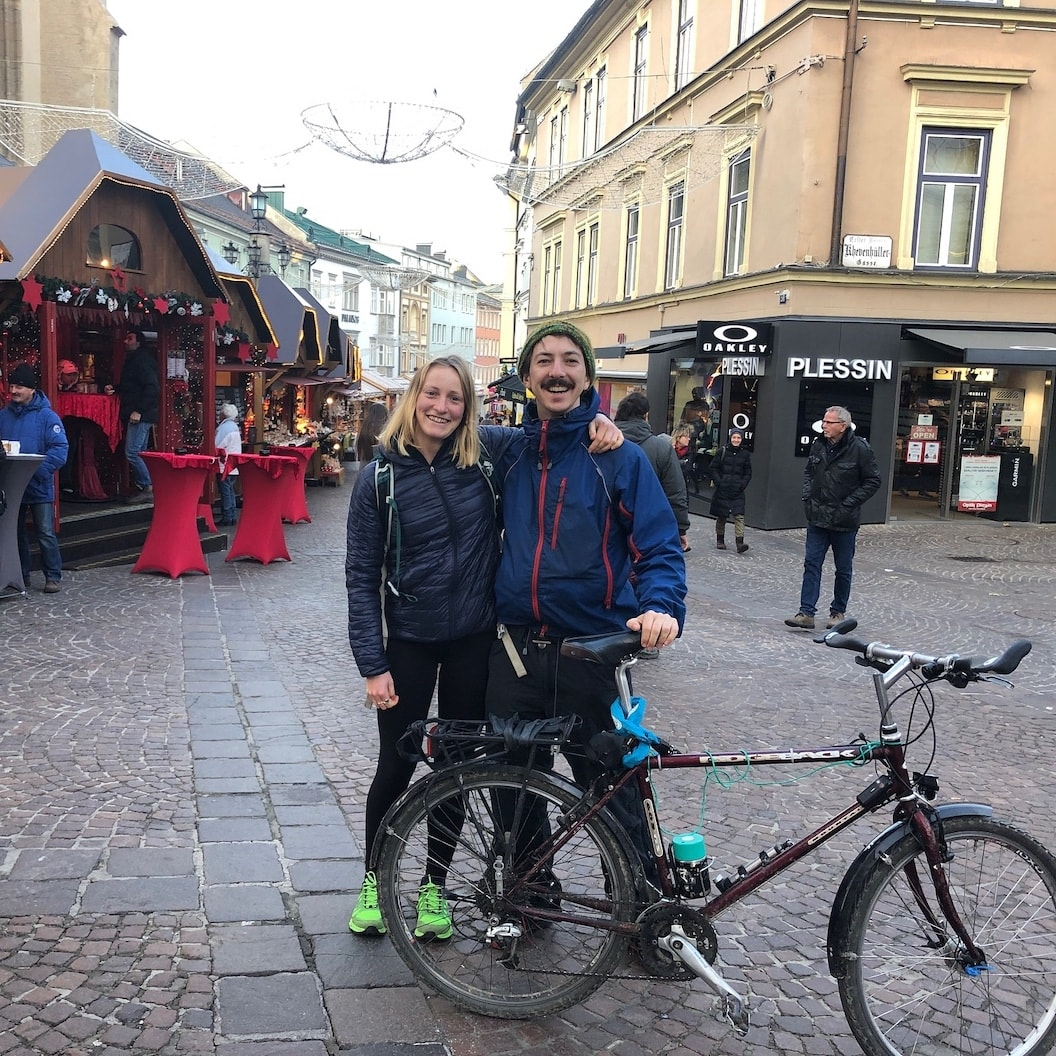 Picture shows Rosie and Mike with their arms around each other, smiling. They are in a city centre and mike is holding his bike.