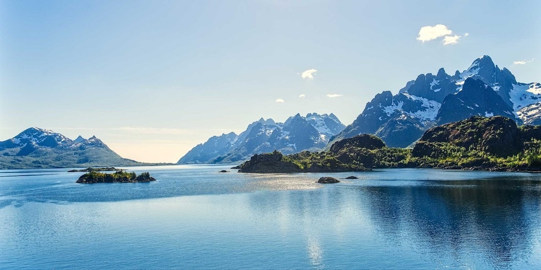 The Norway coastline with clear water and snow on the mountains