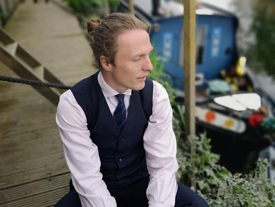 Picture shows Paul wearing a shirt, waistcoat and tie, sitting on decking next to his narrow boat on a canal. There are shrubs in the background and he is looking pensively away from the camera.