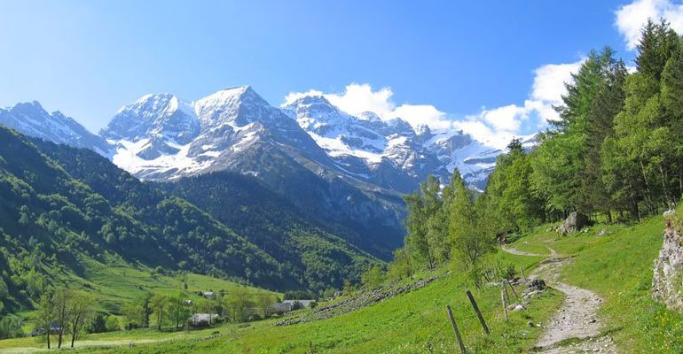 Picture shows the Pyrenees mountains. There is a lush green grassy valley with trees lining the sides. The hills of the valley lead up to the Pyrenees mountain range and the peaks are covered in snow. The sky is bright blue with a few clouds.