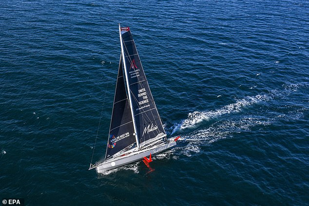 Picture shows the small racing boat Malizia II. It is small, narrow and white with dark navy sails. The sea around it is a deep indigo blue.
