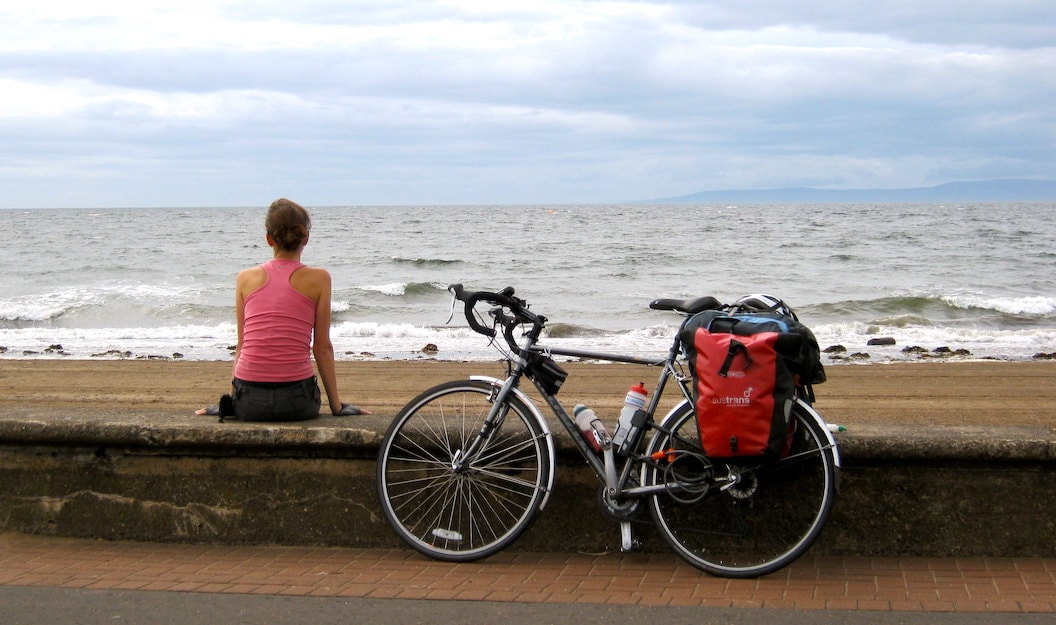 Anna sits with her back to the camera on a low wall separating the beach from the promenade. The beach is sandy and the waves and sky are moody and grey. Next to Anna resting against the wall is her bike.