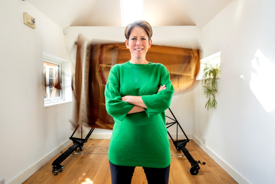 Sarah stands with her arms crossed wearing a bright green dress. In the background an 'inside-out' piano spins on a frame.