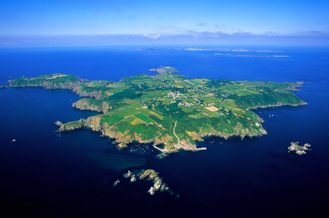 Image shows the island of Sark, a small, green island in a blue sea