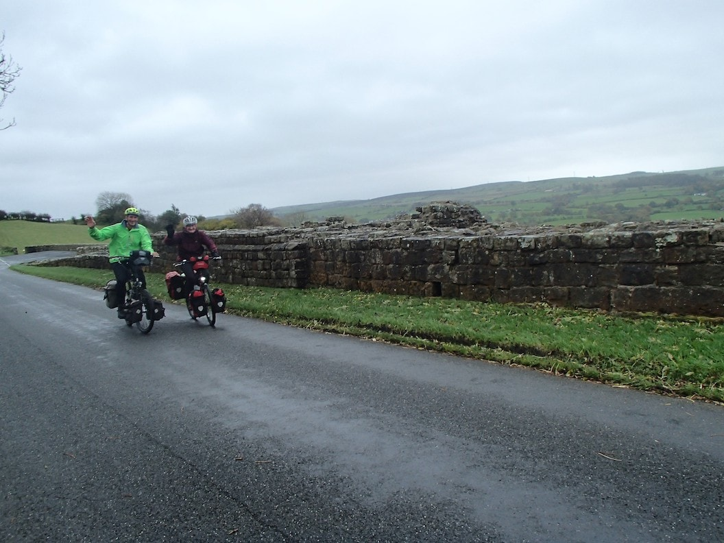 Picture shows Christine and Peter cycling next to Hadrians Wall. It is a gloomy day and the sky is overcast. There are fields in the background.
