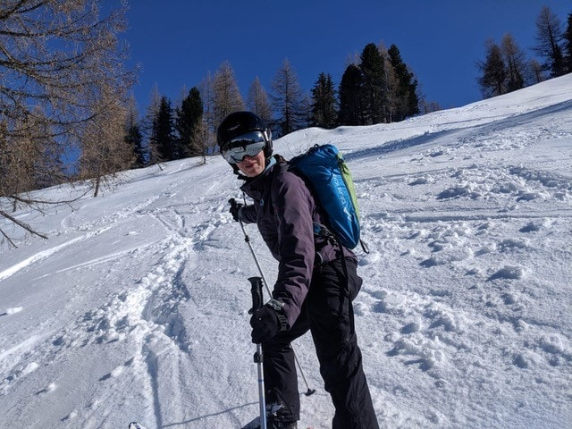 Picture shows skier facing the camera. She is wearing full ski gear including mirrored sunglasses and helmet. Behind them is and expanse of white snow with pine trees in the background. The sky is deep blue.