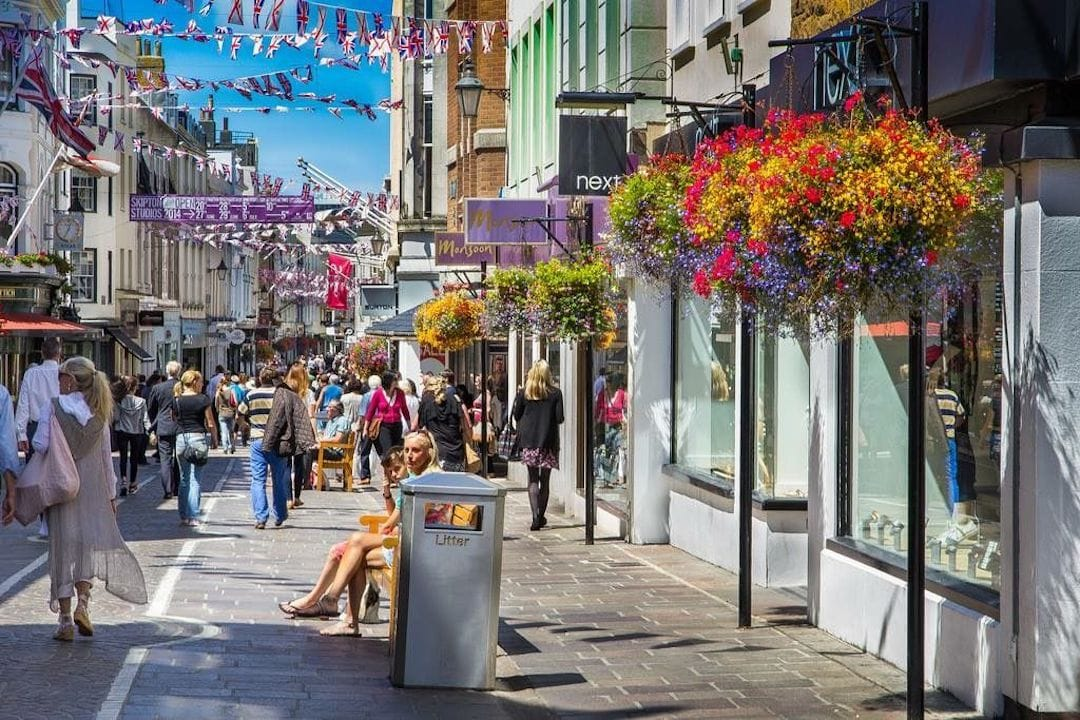 Image shows a busy shopping street in St Helier, with bunting strung across the street and lots of people out and about