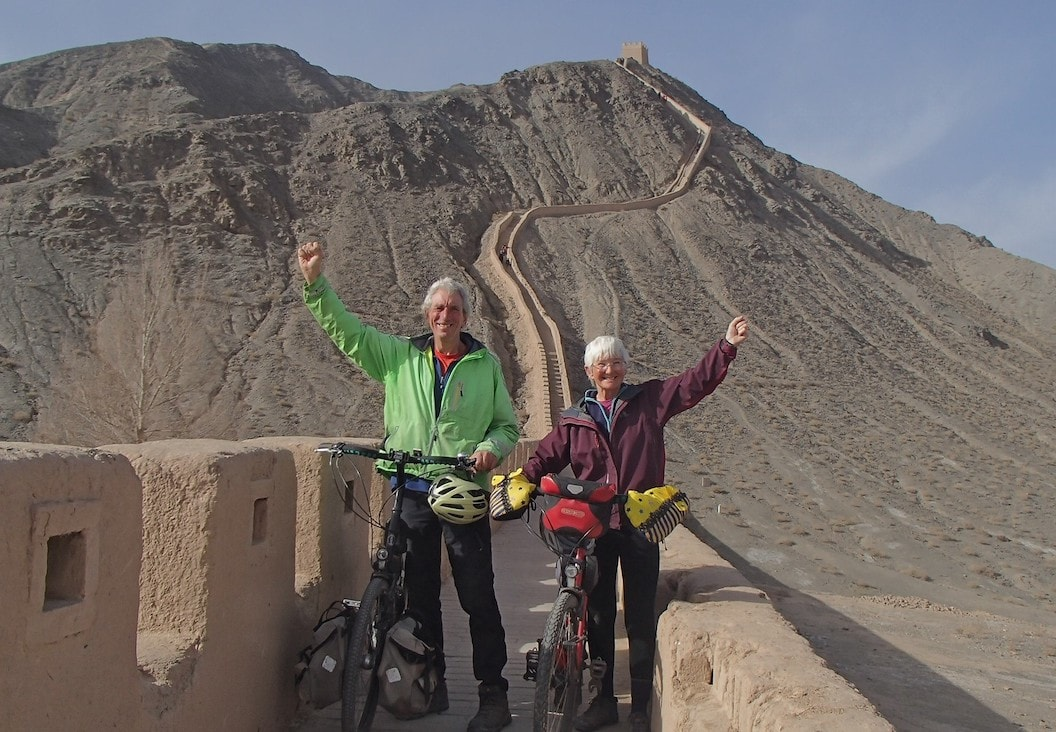 Picture shows Christine and Peter on a dusty and pale red part of the Great Wall of China. They are both holding their bikes with one hand and holding their fists in the air with the other. Peter is wearing a green coat and Christine is wearing a burgundy one.