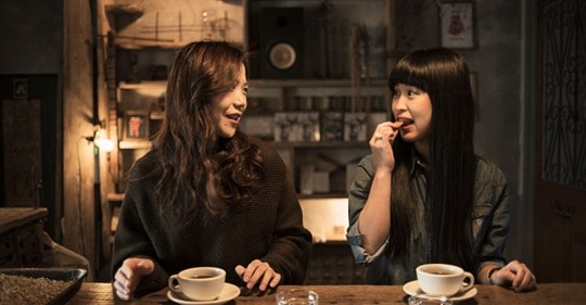 Two women sit at a bar, each drinking a coffee. They are turned towards each other and talking. One of them has a surprised facial expression and is about to eat a biscuit.