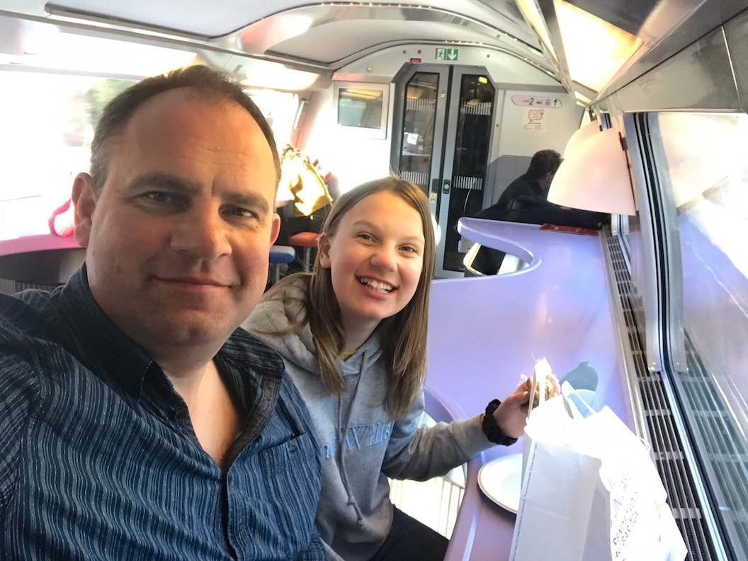 Picture shows Tom and his daughter taking a smiling selfie inside the cafe carriage of their train.