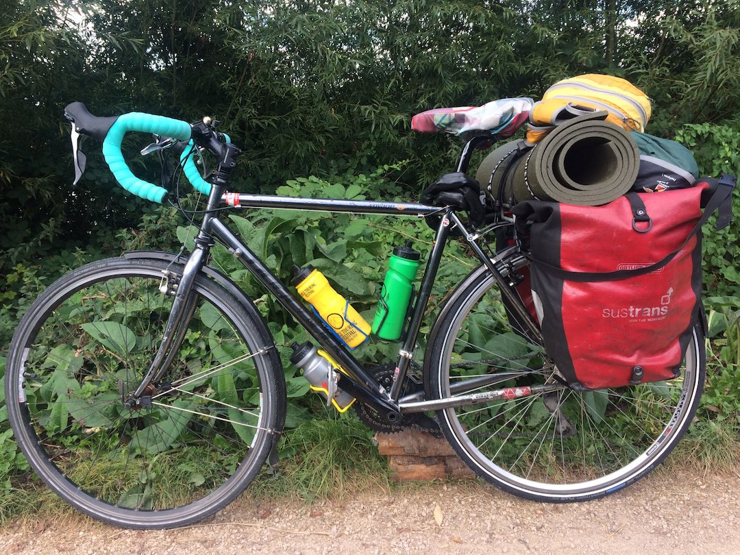 A touring bicycle loaded with panniers, tent and roll mat
