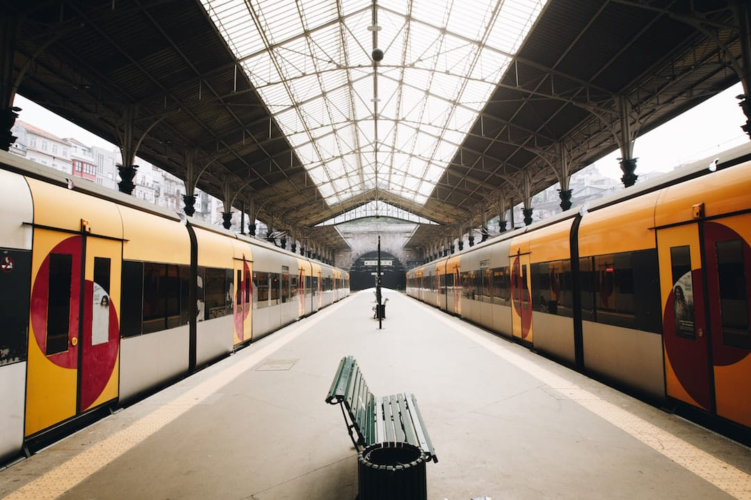 Picture shows two stationary trains wither side of platform at a train station in Portugal. Theres a bench in the middle of the platform and the roof has large rectangular windows.
