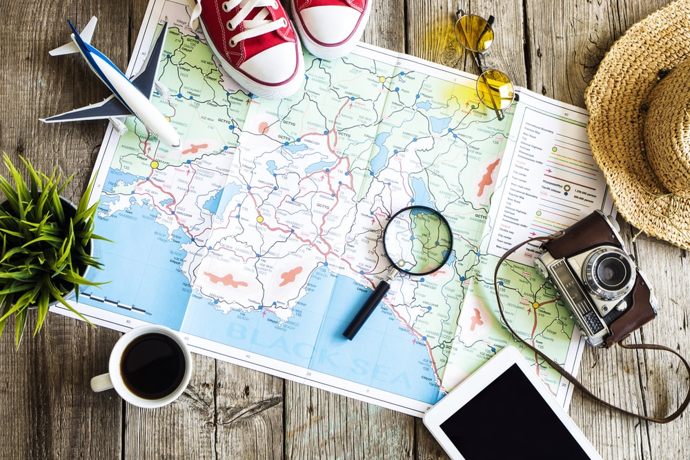 The picture shows a map spread on a wooden table. Surrounding the map is a mug of coffee, a magnifying glass, a camera and a sunhat. The picture is intended to depict travel planning.